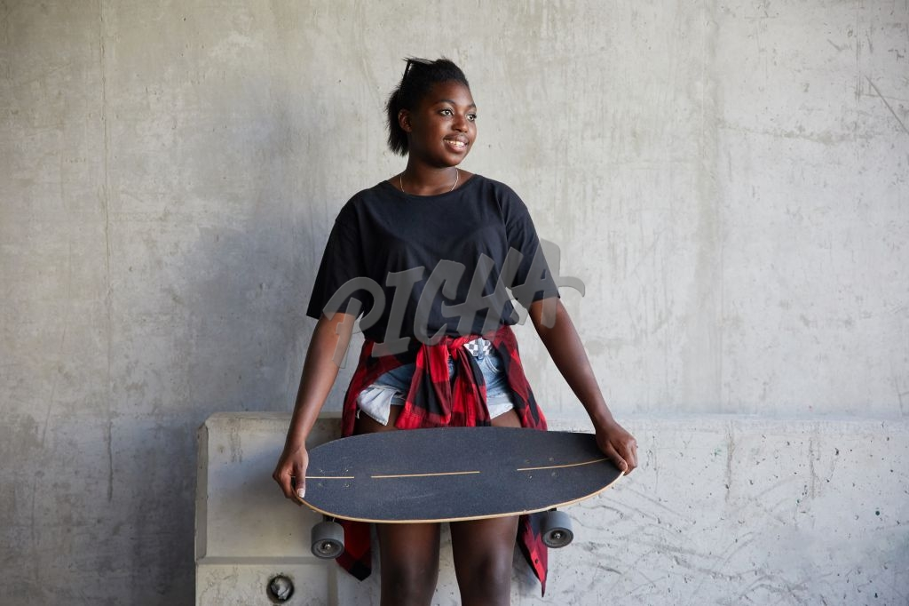 Young girl holding skateboard