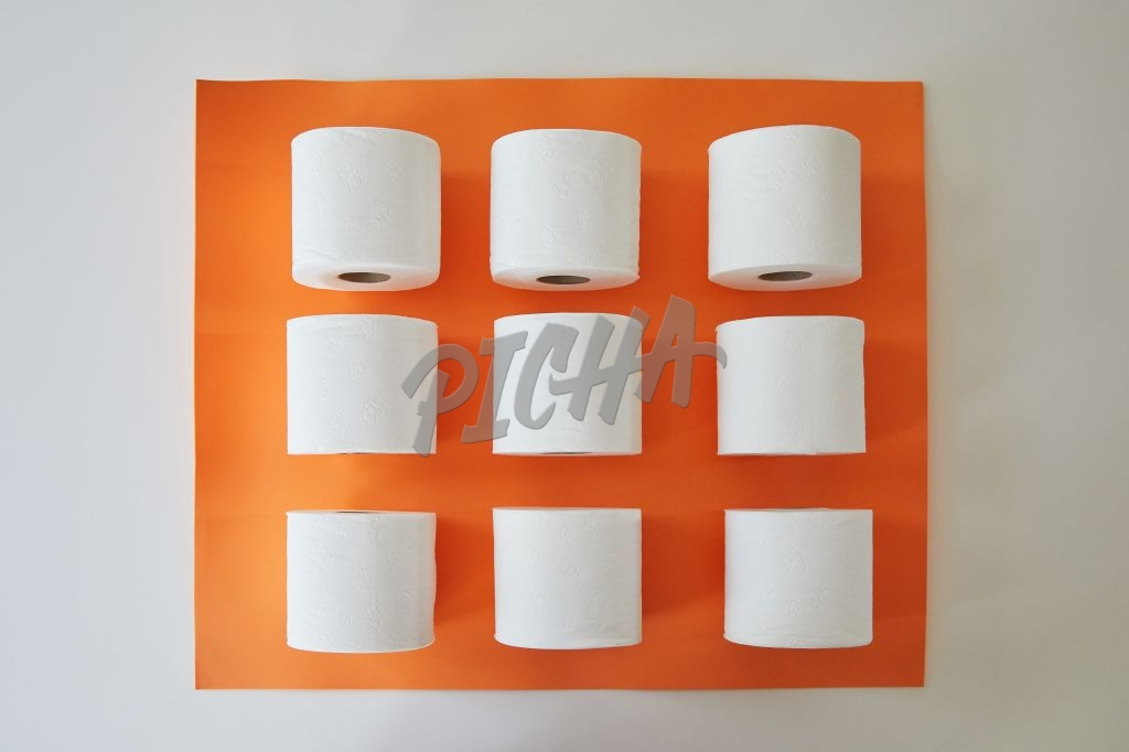 Flatlay of toilet paper on orange background