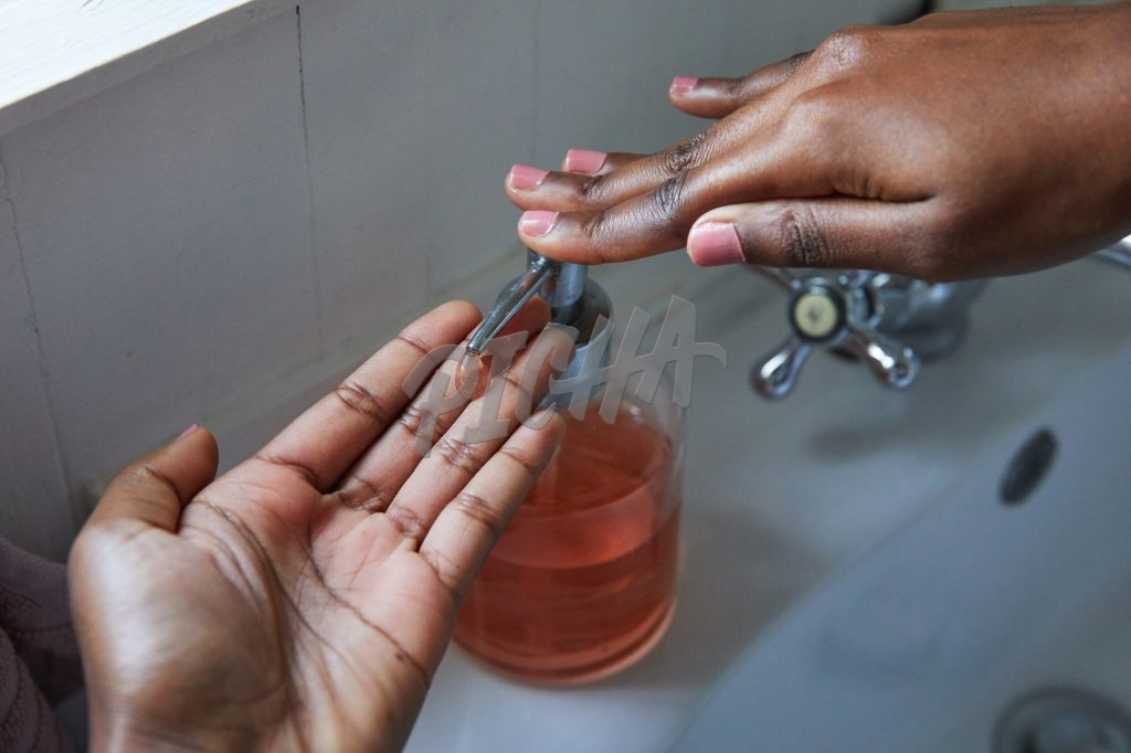 Close up of woman's hands pressing pump bottle of soap