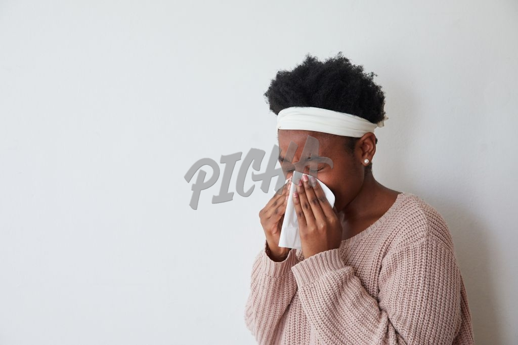 Sick woman sneezing into tissue