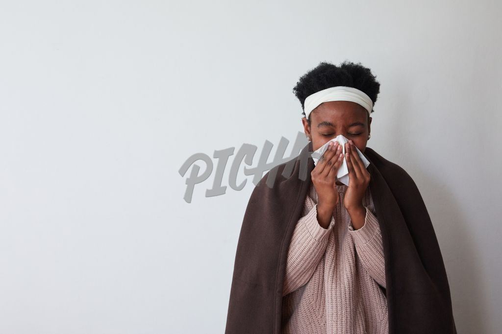 Sick woman sneezing with blanket over shoulders