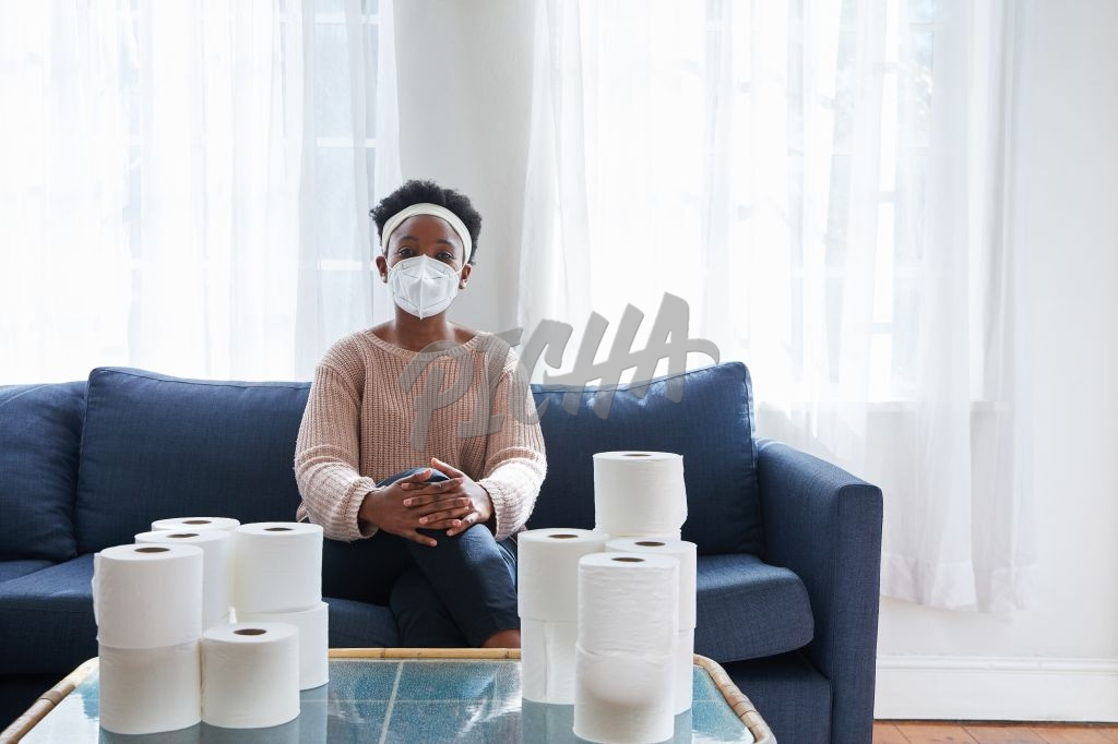 Woman in N95 mask sitting on couch surrounded by toilet paper