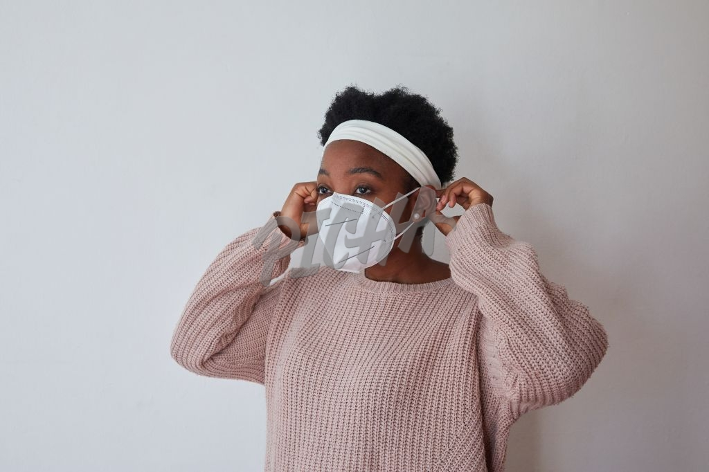 Woman putting on an N95 mask