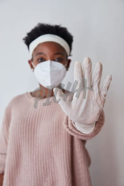 Woman holding up hand wearing surgical glove in N95 mask