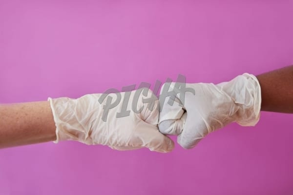 Surgical gloves fist bumping on pick background