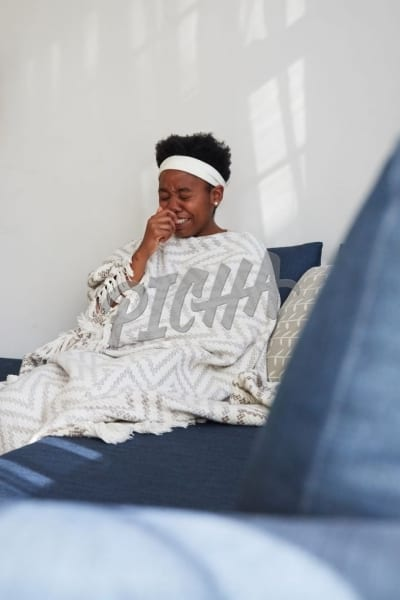Sick woman on couch under blanket sneezing