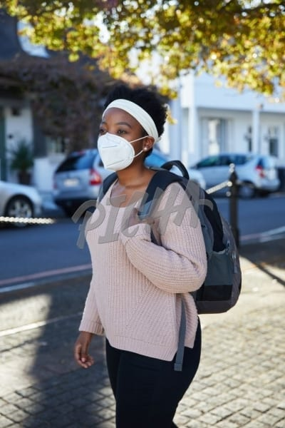 Woman walking in street wearing an N95 mask and backpack in street