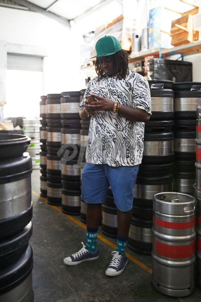 Man standing by kegs while on phone in warehouse
