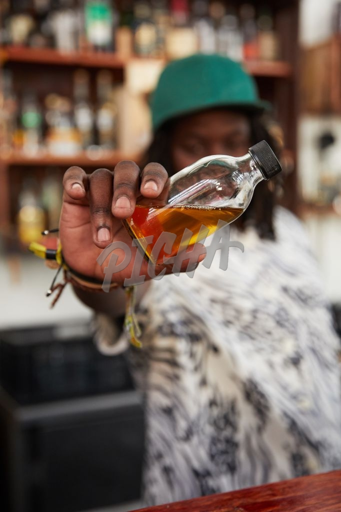 Mixologist holding up cocktail ingredient in bottle at bar