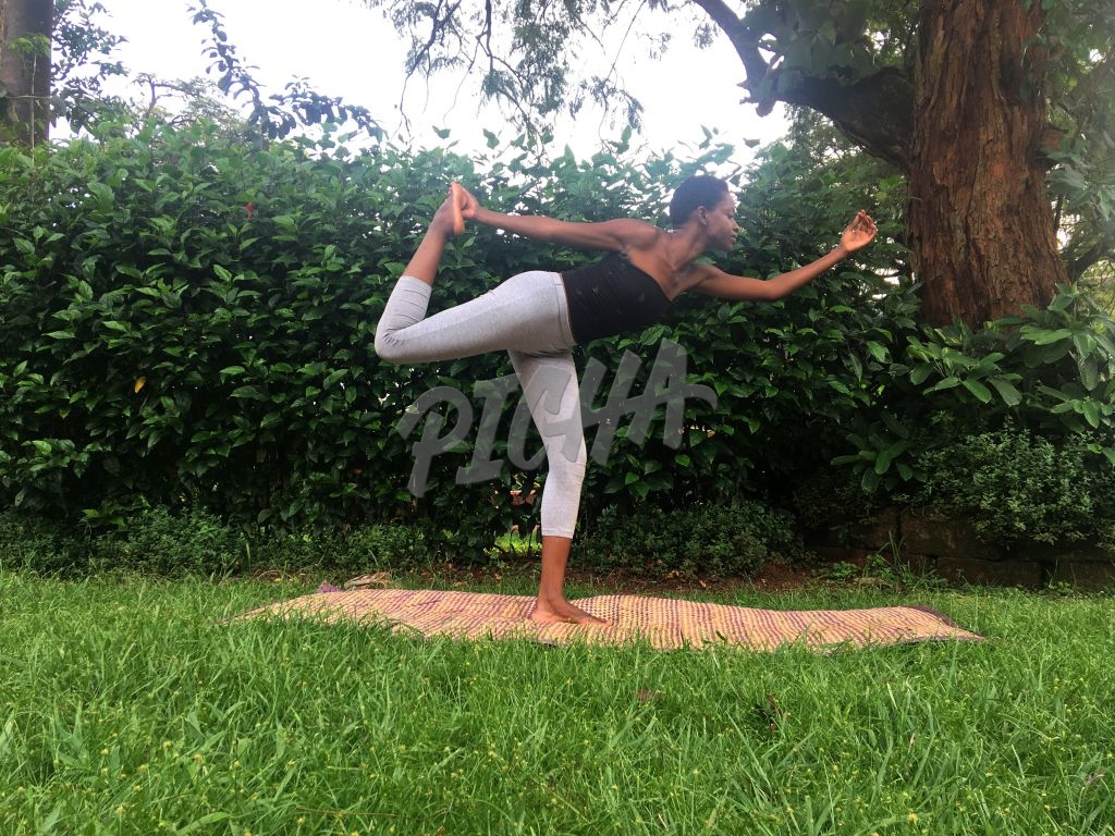 woman practicing yoga in a garden, dancer pose
