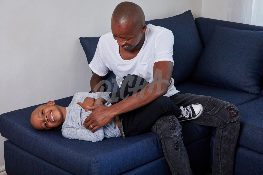 Father and son playing on couch