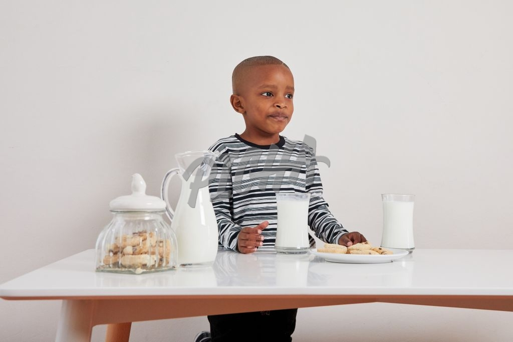 Young boy enjoying milk and cookies
