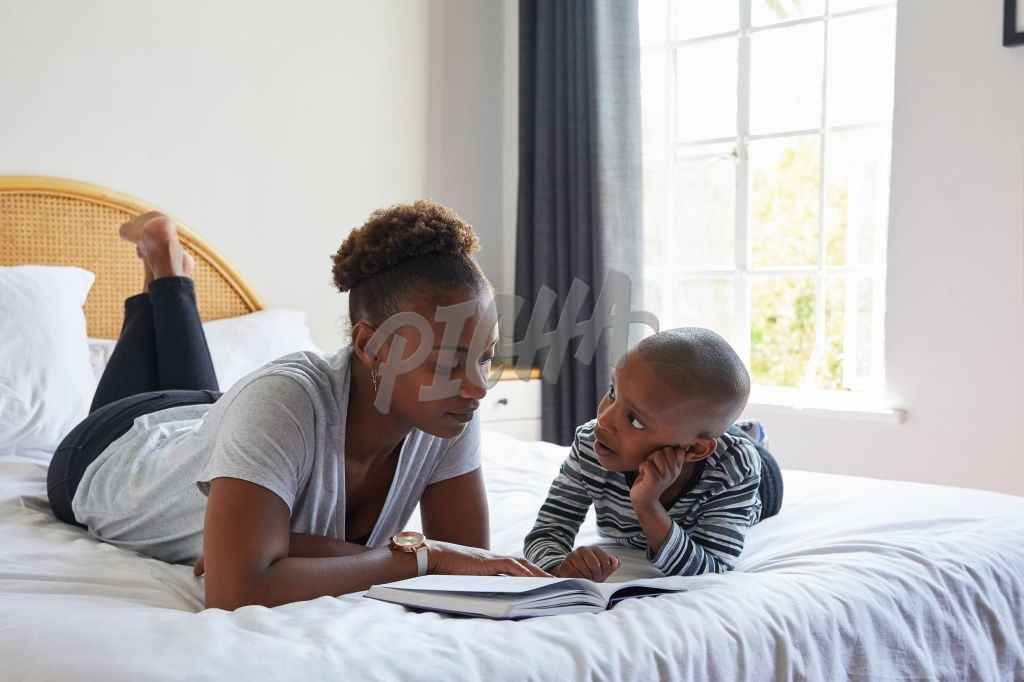 Mom reading to son in bed