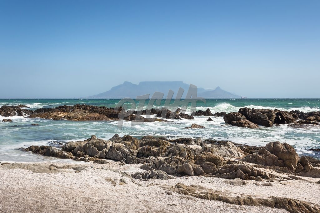 View of Table Mountain with beach, ocean and rocks in foreground