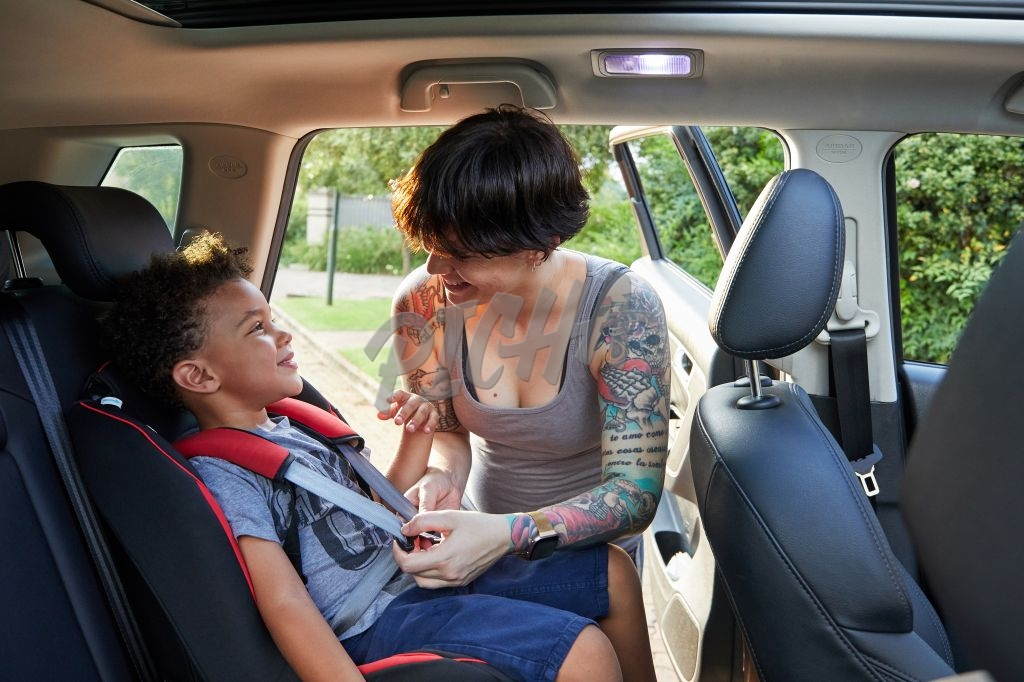 Mother putting son into car seat