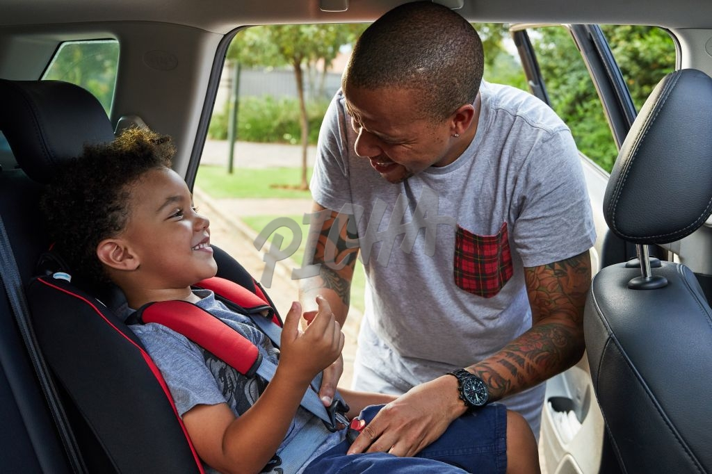 Father putting son into car seat
