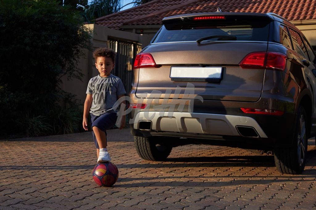 Boy with soccer ball outside home