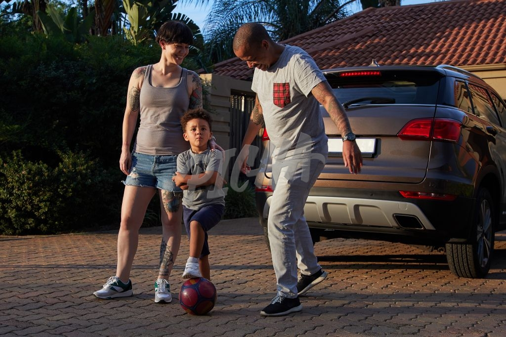Family playing soccer outside home