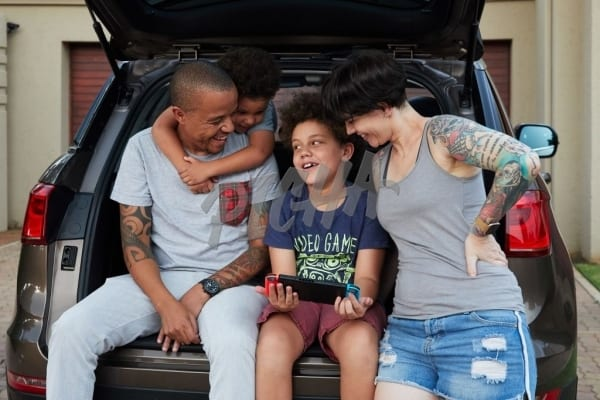 Family relaxing at the back of their car