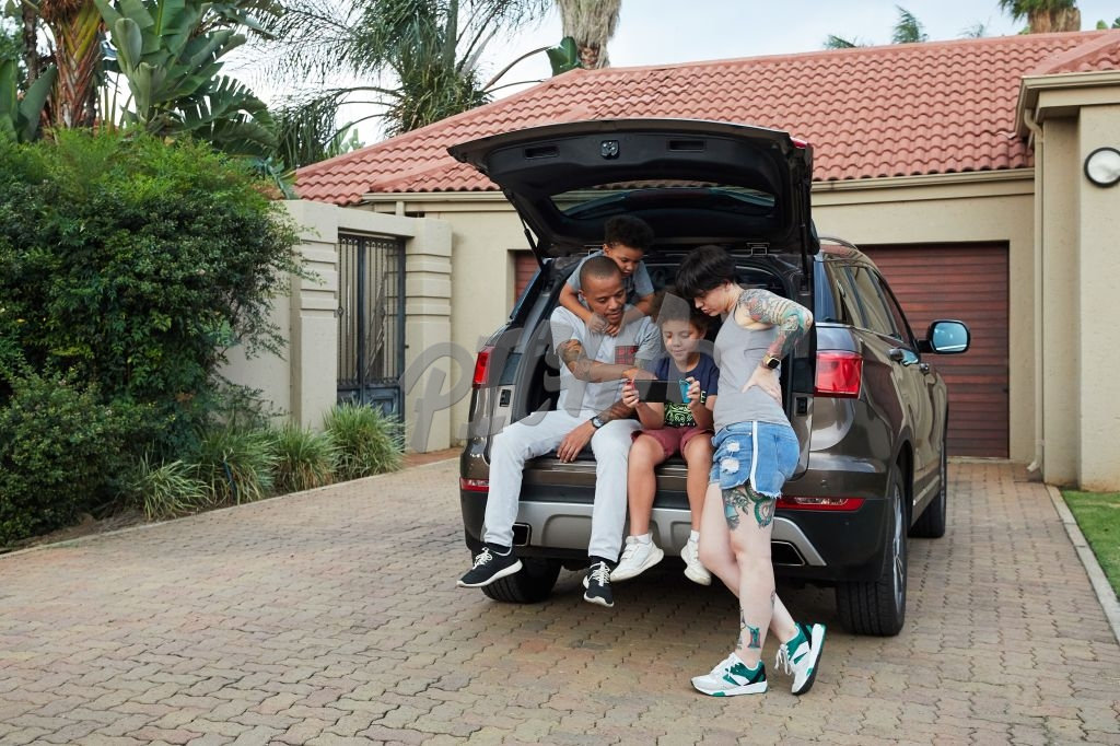 Family relaxing in the boot of their car
