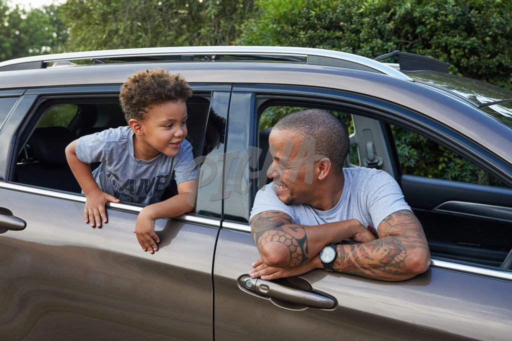 Father and son hanging out of the car