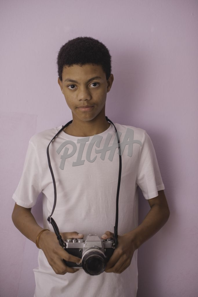 Vertical portrait of teenager holding camera