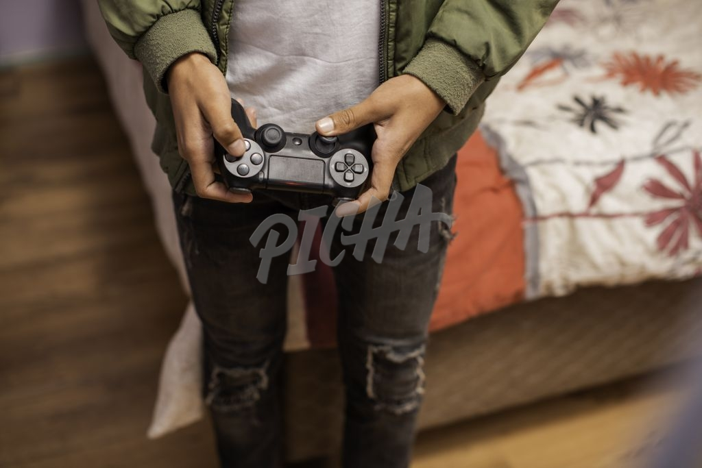 Teenager standing and playing video games