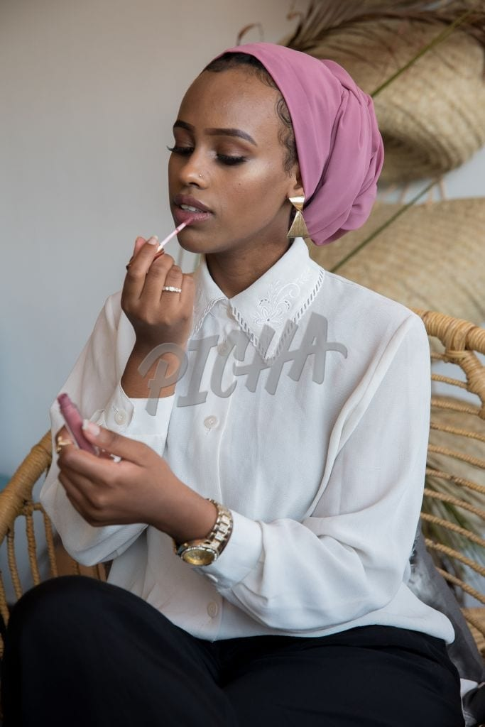 Young lady applying lip gloss