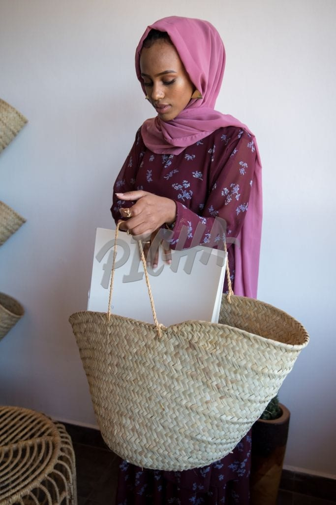 young woman putting paper in a basket