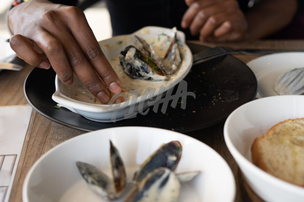 Close up shot of person using hand to eat mussels