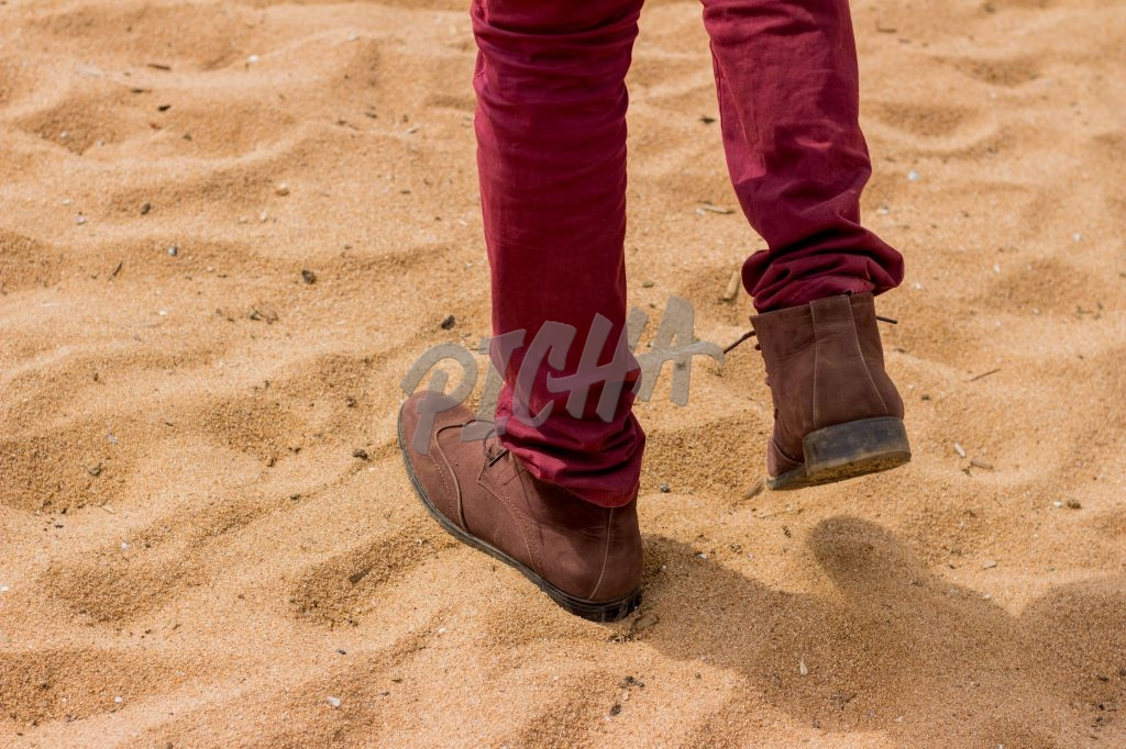 A man comfortably walking on a beach with nice shoes
