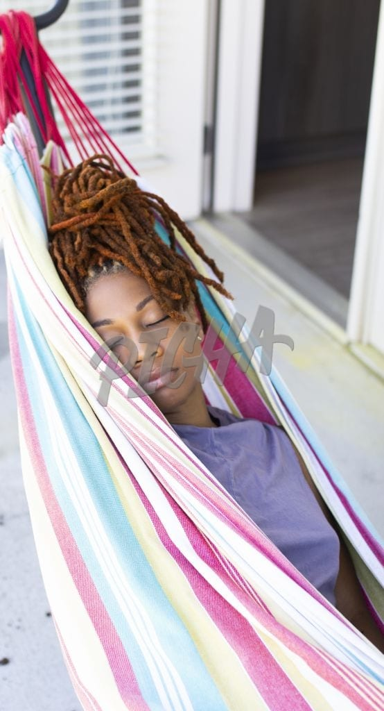 Young woman sleeping on a hammock