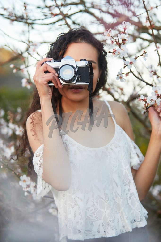 Woman with film camera taking pictures