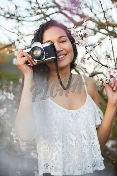 Happy woman with film camera taking pictures