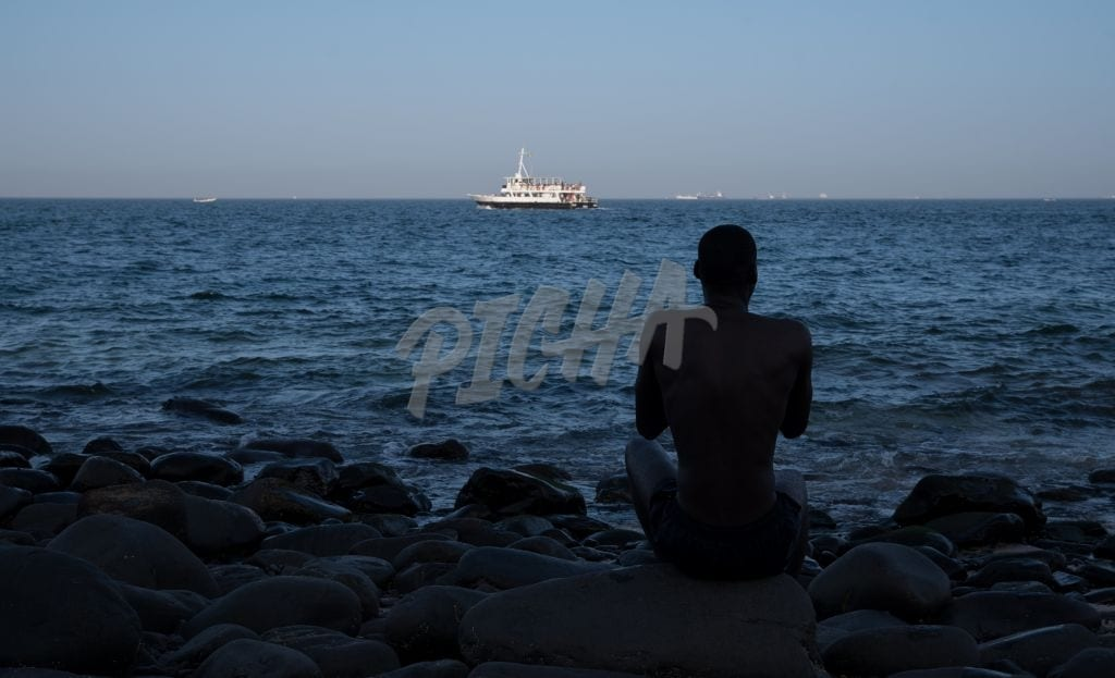man looking at a boat