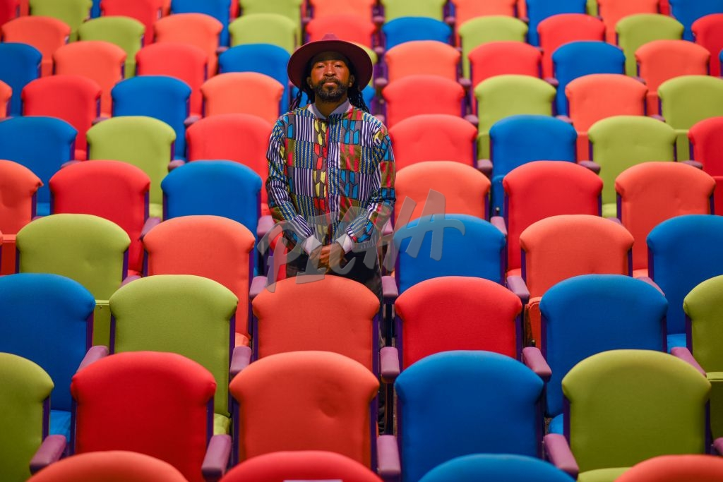 Stylish African man standing between colorful chairs in empty theatre