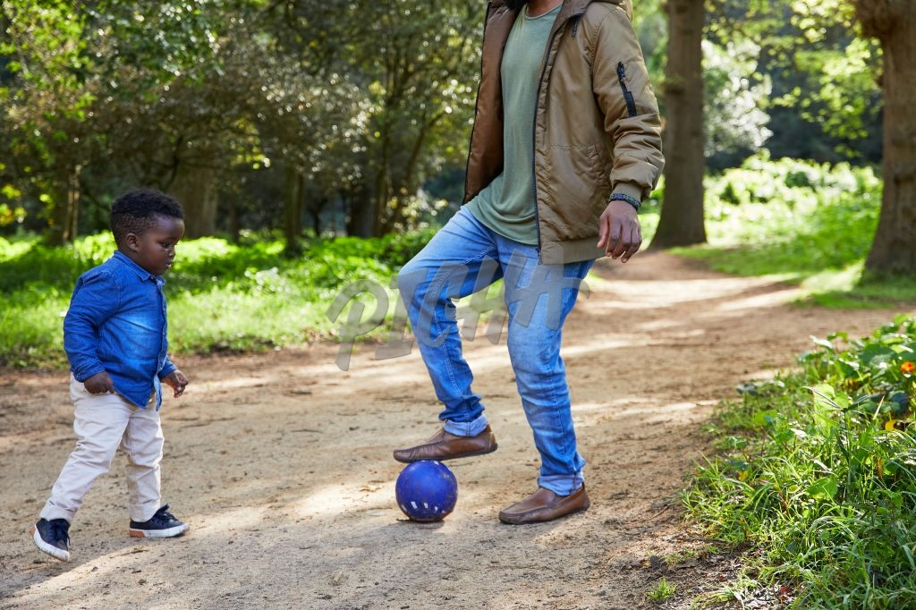 Father and son playing kicking a ball around