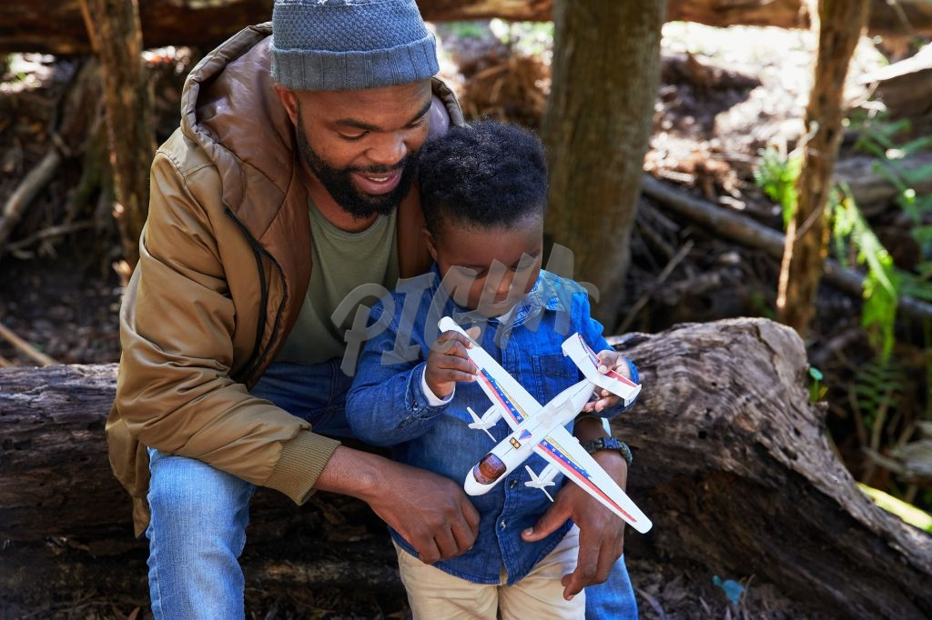 Father and son playing with a toy plane