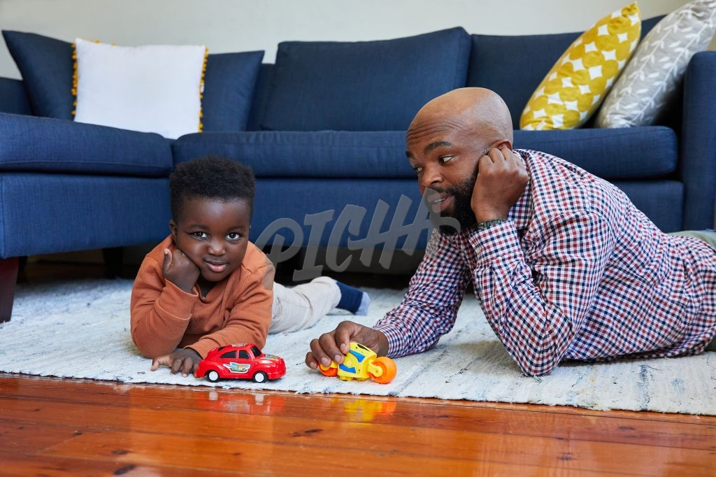 Father and son bored while playing toy cars