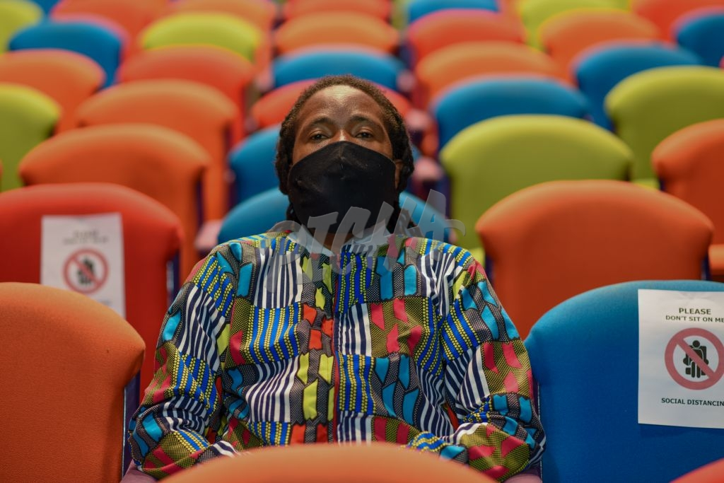 One person sitting alone in theater with mask on