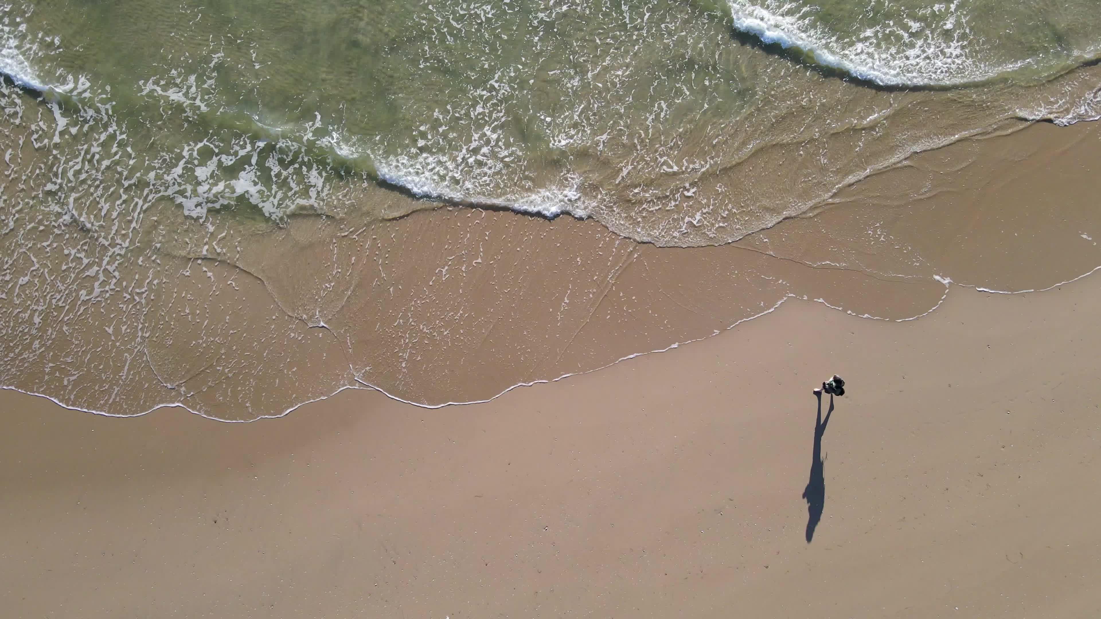 Aerial view of person walking along coast
