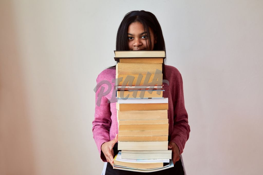 Gen Z teen girl holding a pile of books