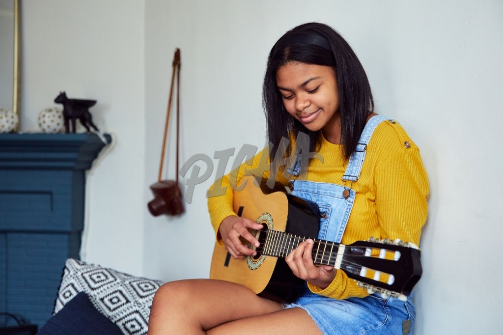 Gen Z teen girl at home playing guitar