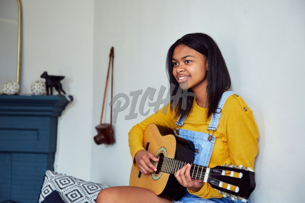 Gen Z at home playing guitar