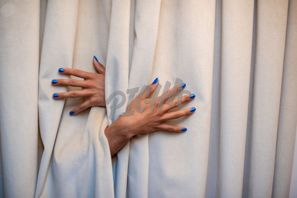 hands with blue nail polish protruding from behind curtains