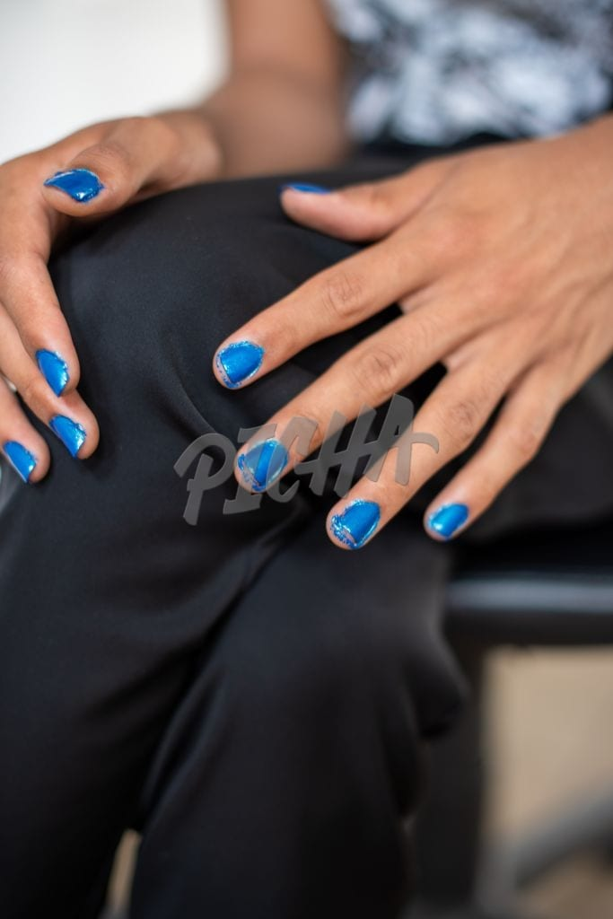 Close up shot of young queer person whose nails are painted blue