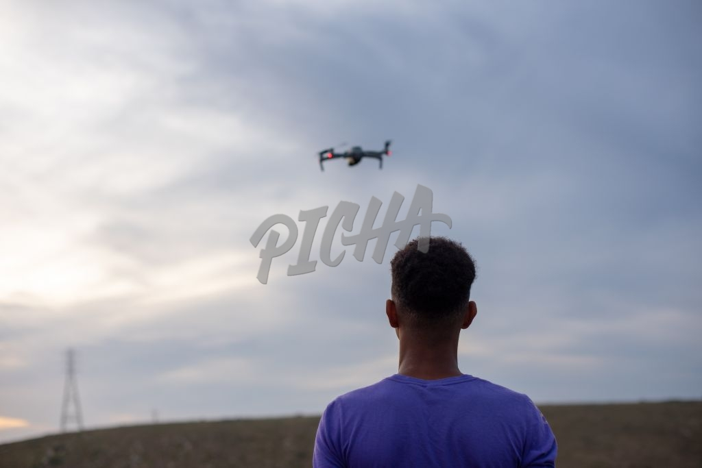 Rear view of young boy flying a drone