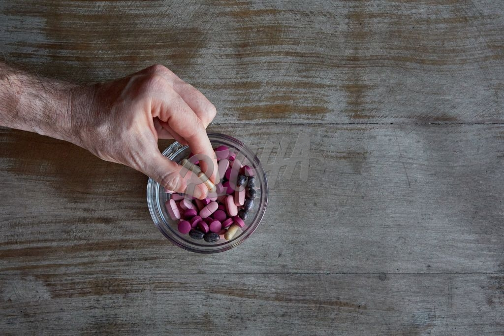 an holding a single pink tablet over a bowl of tablets