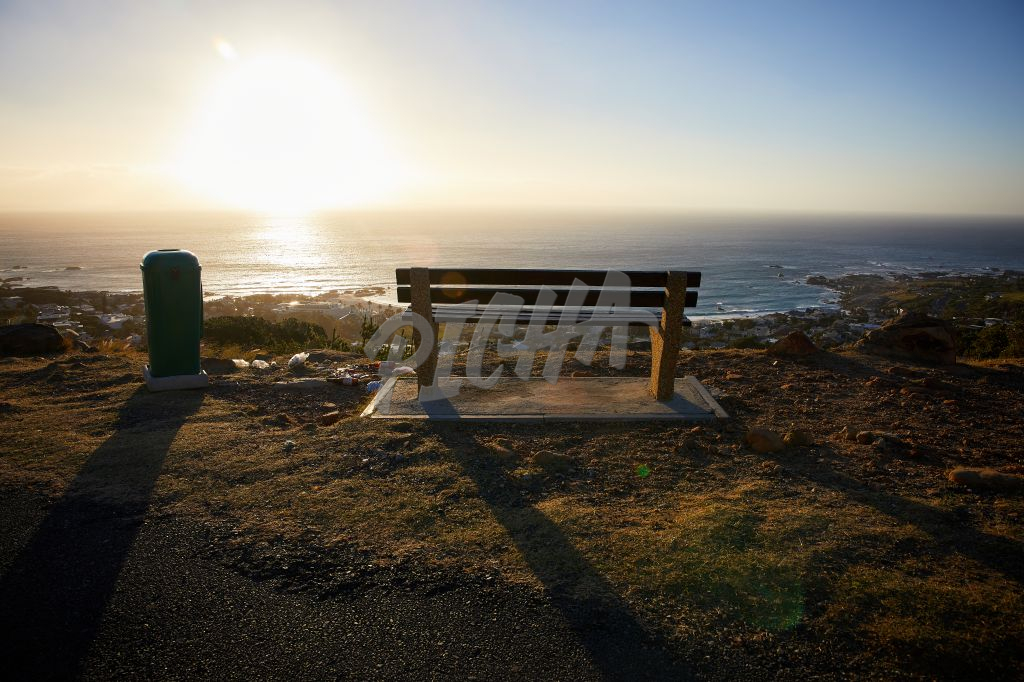 Empty bench at sunset next to overflowing dustbin