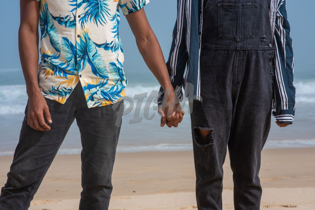 Midsection shot of couple holding hands at beach